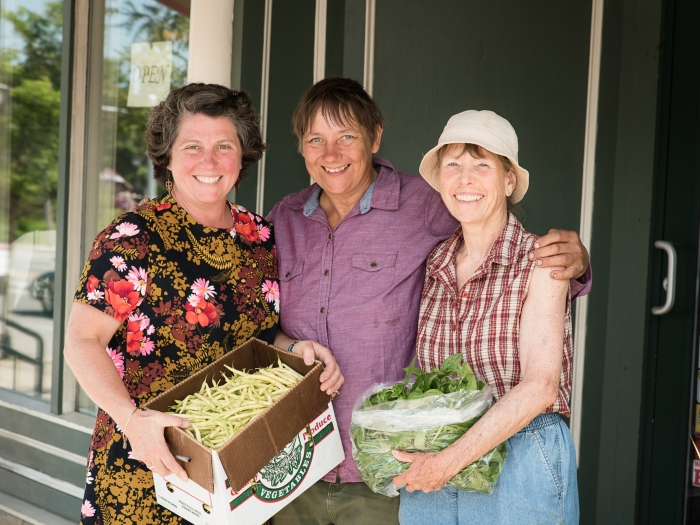 Three women stand together, two holding boxes of produce